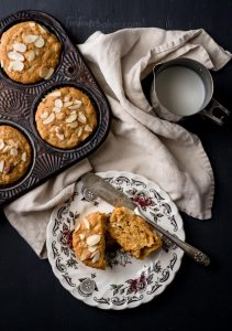 Fresh muffins in a vintage pan. One cut in half on a china plate