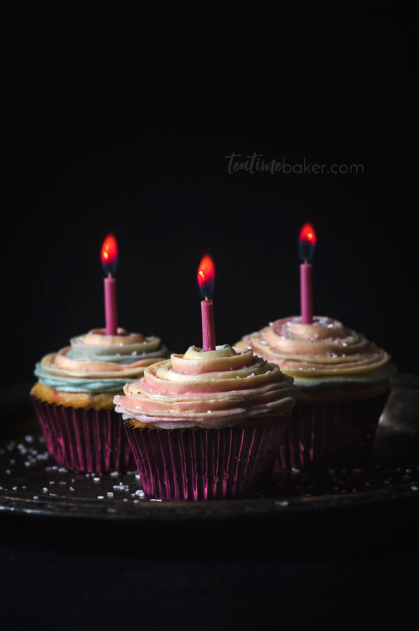 Three colorful cupcakes with pink candles and colored flames