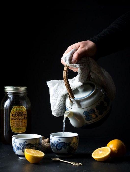 Pouring lemon ginger tea from a teapot into chinese style teacups