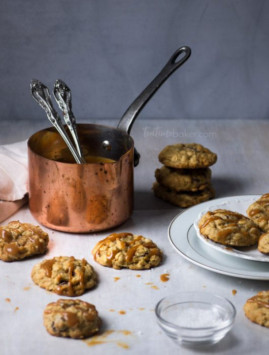 Salted Caramel Chocolate Chip Cookies spread around a copper pan of caramel