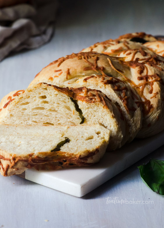 A braided loaf of basil parmesan bread sliced and ready to eat.