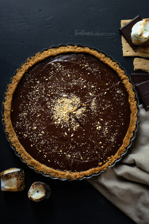 A Dark Chocolate S'mores Tart with toasted marshmallows and dark chocolate squares around it