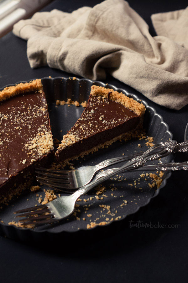 A Dark Chocolate S'mores Tart with 3 forks in the tin and a sliced piece