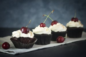 Deep dark chocolate cupcakes with freshly whipped cream, a cherry and a sprinkling of cinnamon | Black Forest Cupcakes