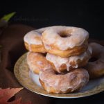 Soft, fluffy delicious homemade yeast doughnuts are dipped in a vanilla glaze to fulfill all your doughnut cravings.   Homemade doughnut recipe   The Teatime Baker   glazed doughnuts #homemadeyeastdonuts