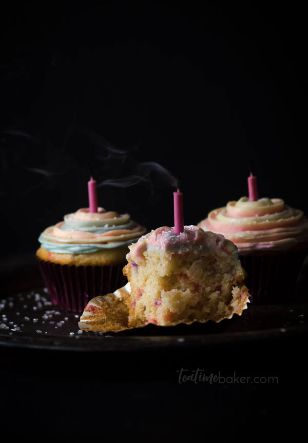The inside of a funfetti cupcake with pink and purple sprinkles and smoke from a blown out candle.