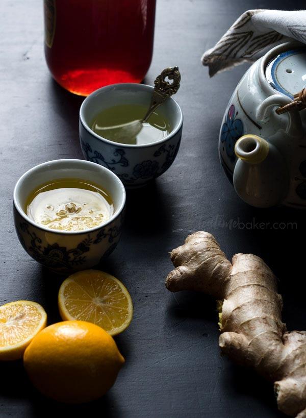 Blue and gray teapot with small glasses of lemon ginger tea, fresh lemons, fresh ginger, and honey