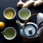 Blue and gray teapot with three small glasses of lemon ginger tea