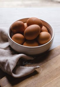 Bowl of brown eggs in a pottery bowl with a linen napkin