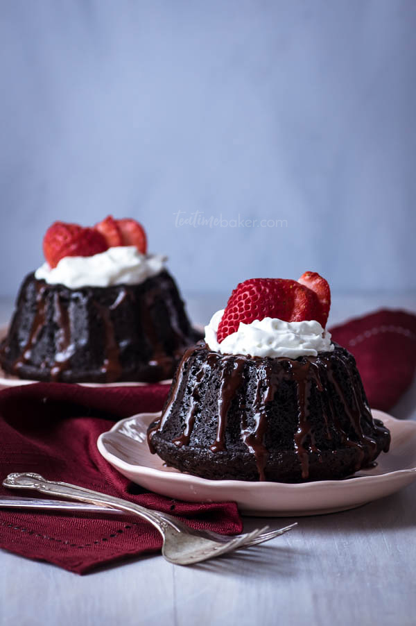 Two mini dark chocolate cakes topped with whipped cream and strawberries