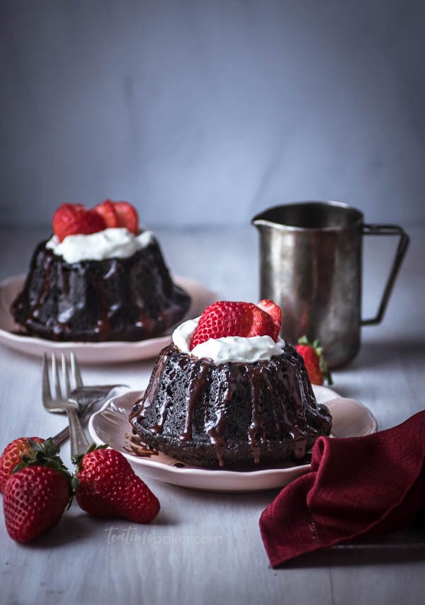 Two mini chocolate bundt cakes with espresso ganache, whipped cream and a sliced strawberry