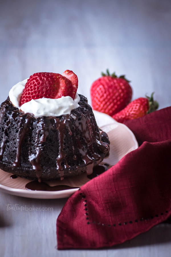 A closeup of a mini chocolate bundt cake with espresso glaze, whipped cream and a sliced strawberry