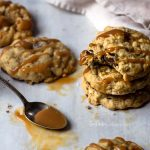 Stacked Salted Caramel Chocolate Chip Cookies with a spoon to drizzle caramel on top.