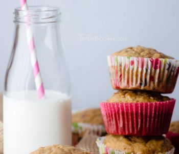A delicious stack of Healthy Breakfast Muffins in spring papers by a glass of milk