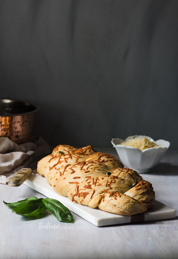 A loaf of basil parmesan bread on a cutting board ready to slice