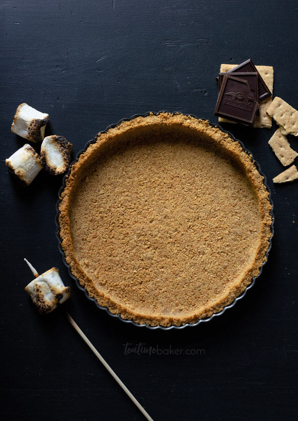 An empty graham cracker crust next to dark chocolate squares and toasted marshmallows