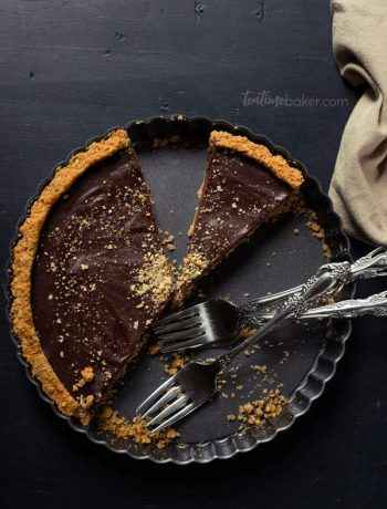 A sliced Dark Chocolate S'mores Tart with several forks in the tin