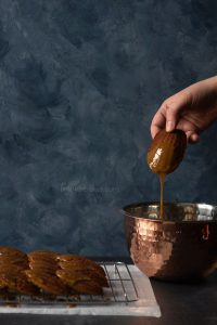 Gingerbread Madeleine being dipped into glaze