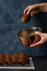 Gingerbread Madeleines being dipped into a bowl of glaze