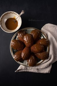 A plate of Gingerbread Madeleines with a bowl of glaze