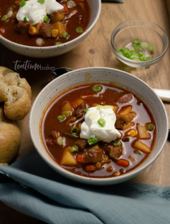 Two bowls of beef stew with sour cream and green onions