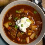 Bowl of Sunday Afternoon Irish Beef Stew with sour cream and green onions