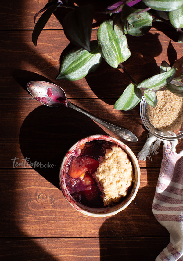 Singe dish of blueberry peach cobbler on a table with sunshine, a spoon and a plant
