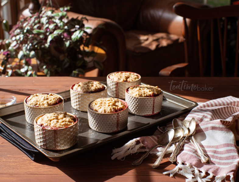 6 ramekins of homemade berry cobbler on a tray in a sunny room