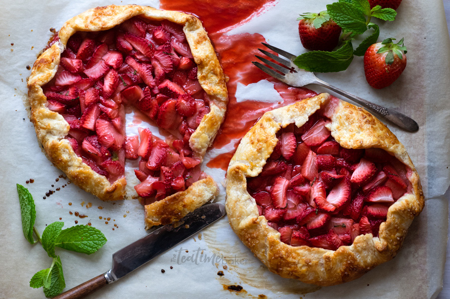 Two rustic strawberry galettes ready to serve with fresh mint
