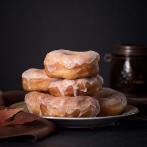 A stack of fresh donuts with glaze dripping down the sides