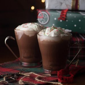 Two glasses of hot chocolate with fresh whipped cream and red and green sprinkles