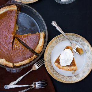 A dish of pumpkin pie with a piece on a plate topped with whipped cream